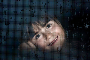 A child peers through a window screen.